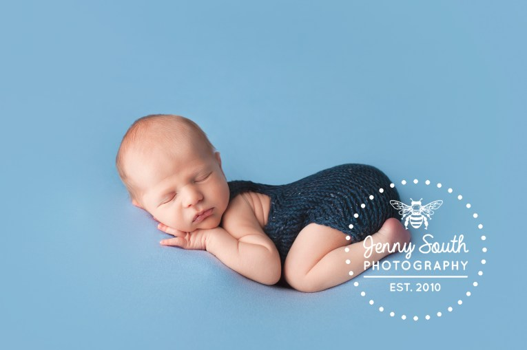 A newborn baby boy sleeps on his tummy against a blue backdrop in a knitted navy romper.