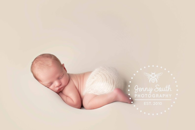 A baby boy is pictured sleeping on a bream backdrop during his newborn photography session.