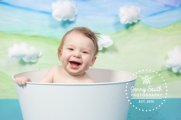 A baby boy giggles with delight during a photo shoot for his first bitrthday.