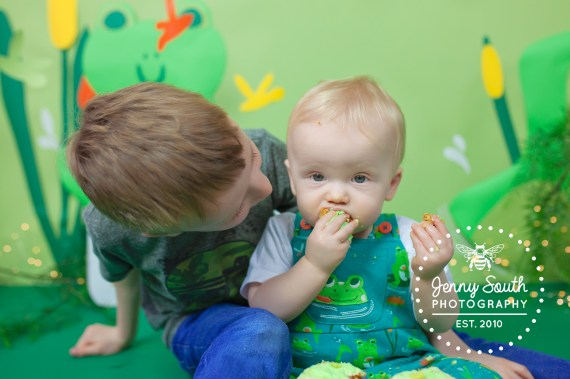 A proud big brother looks lovingly at his little brother as he eats up his birthday cake