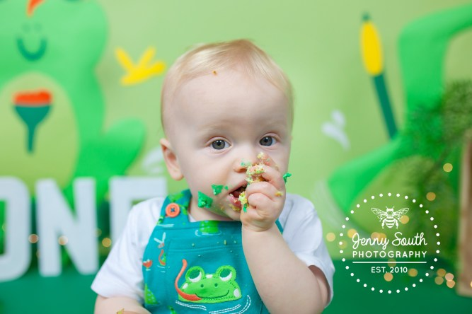 A Baby boy is covered in green icing as he smashed his frog themed birthday cake for a first birthday treat.