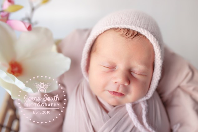 A newborn baby smiles sweetly in her sleep during her newborn session in Plymouth.