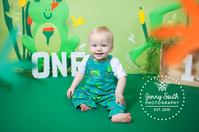 A little boy smiles cheekily as he poses in his swamp themed set for his first birthday cake smash.
