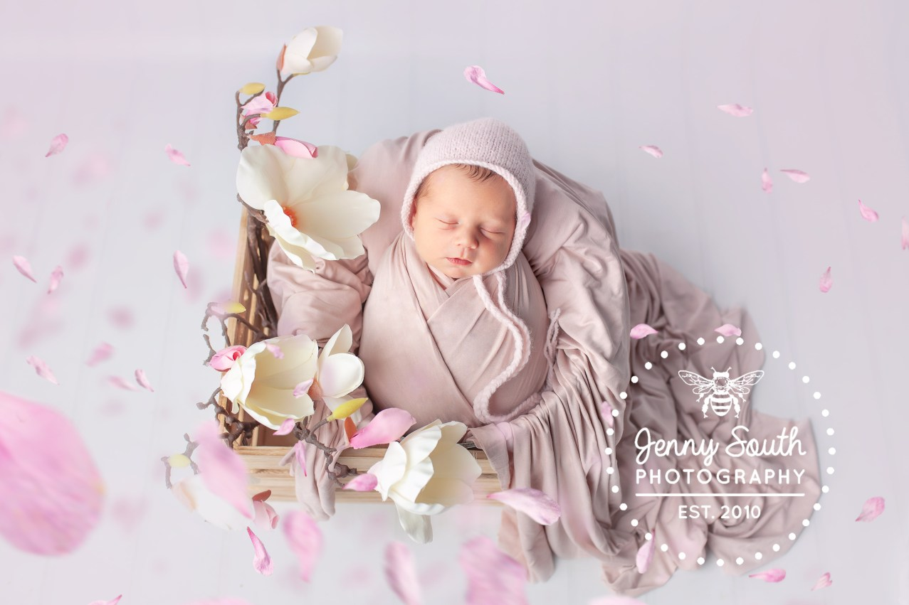 A newborn baby is surrounded by the joys of spring, with magnolias in full boom swirling all around her.
