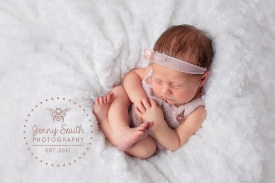 A newborn baby girl wears a matching pink knitted romper and headband in a blue magnolia pink.