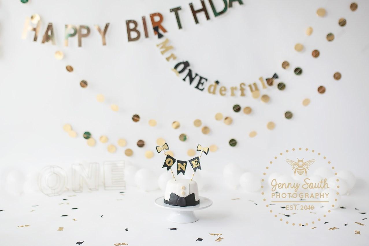 A stunning Mr wonderful cake smash set up, of golds, blacks, and whites.