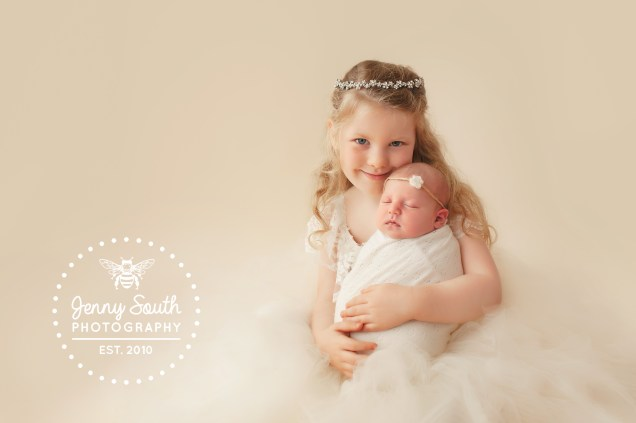 Two beautiful sisters share a special moment during a newborn session in Plymouth