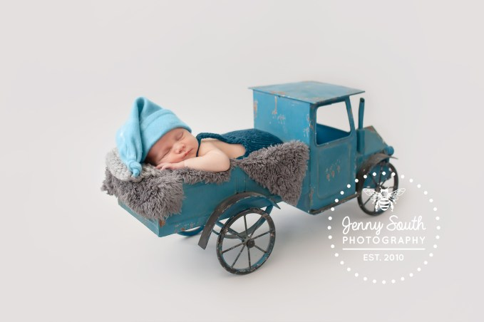 A tiny baby boy naps in a blue vintage truck during his newborn session at the studio