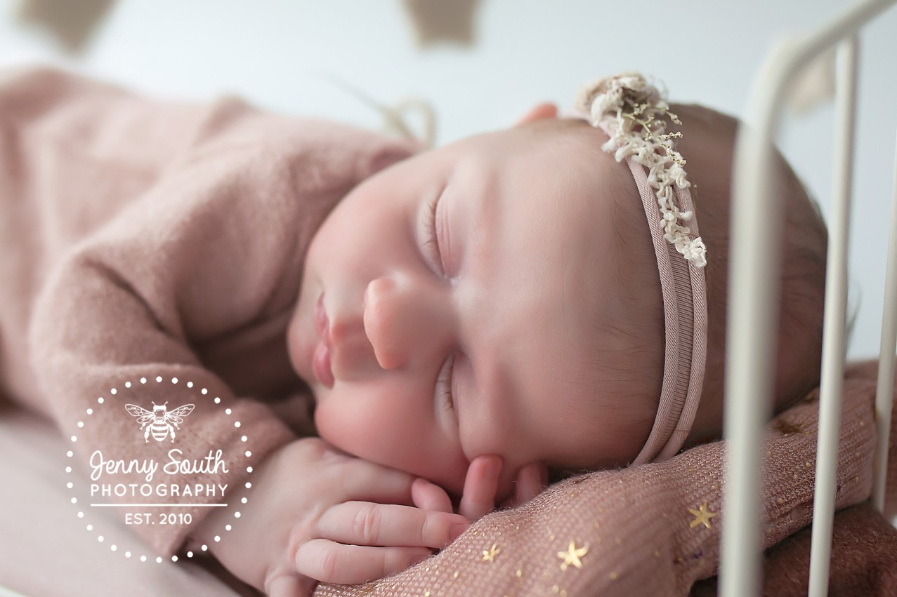 Sleepydust a plenty in our newborn studio in Plymouth. A tiny newborn girl sleeps soundly surrounded by stars.