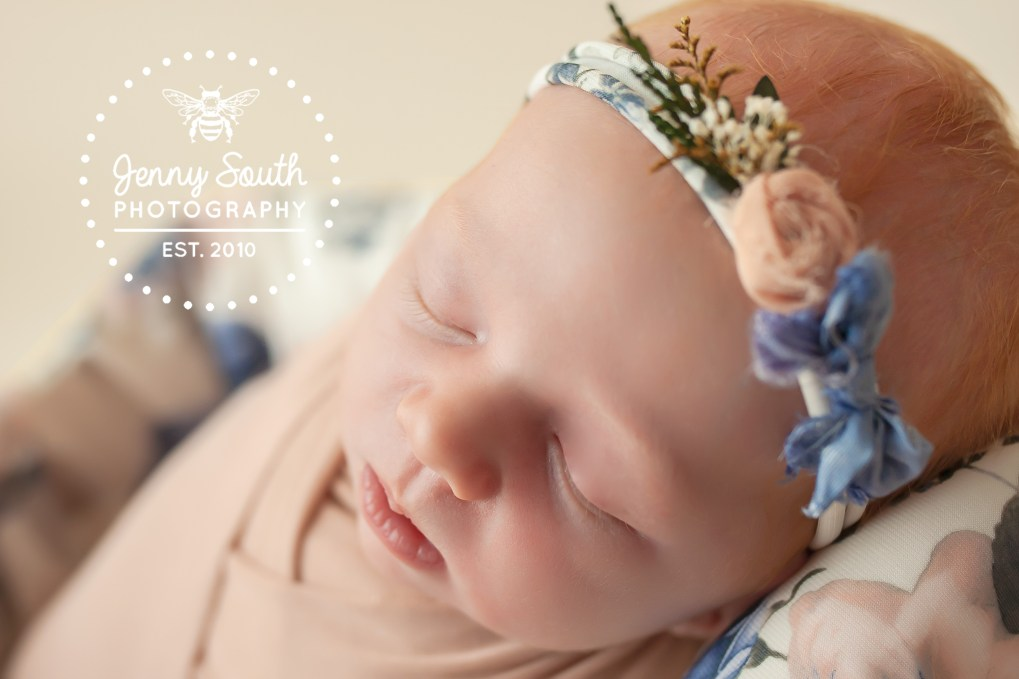 A little newborn baby girl sleeps soundly in a mix of floral hues during her newborn session.