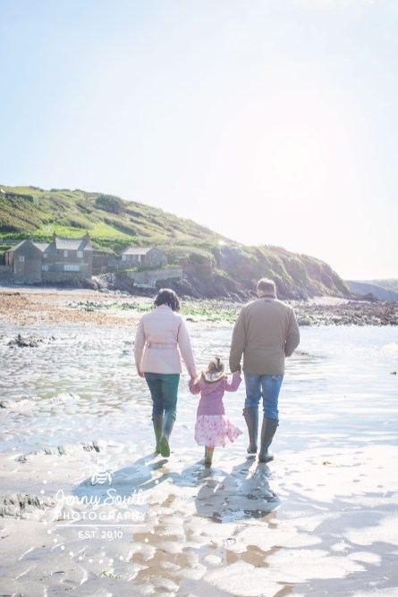 A family stroll hand in hand on the shore of Wembury beach in Devon