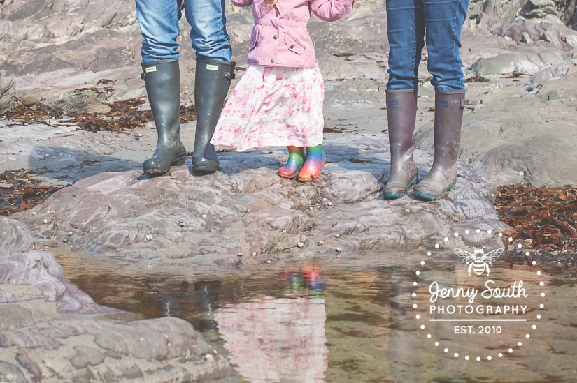 A family stand in they welly boots whilst looking down into one of the many rockpools on Wembury beach