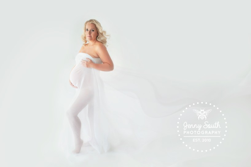 A mother to be is trapped in a sheer fabric which flows behind her during a maternity photo shoot