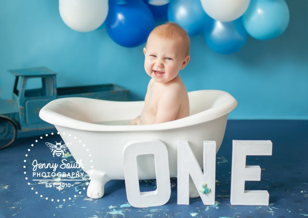 A cheeky little boy gives a cheeky grin as he sits in a roll top mini bath during a photo shoot