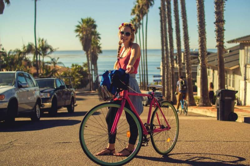 Girl standing by bicycle