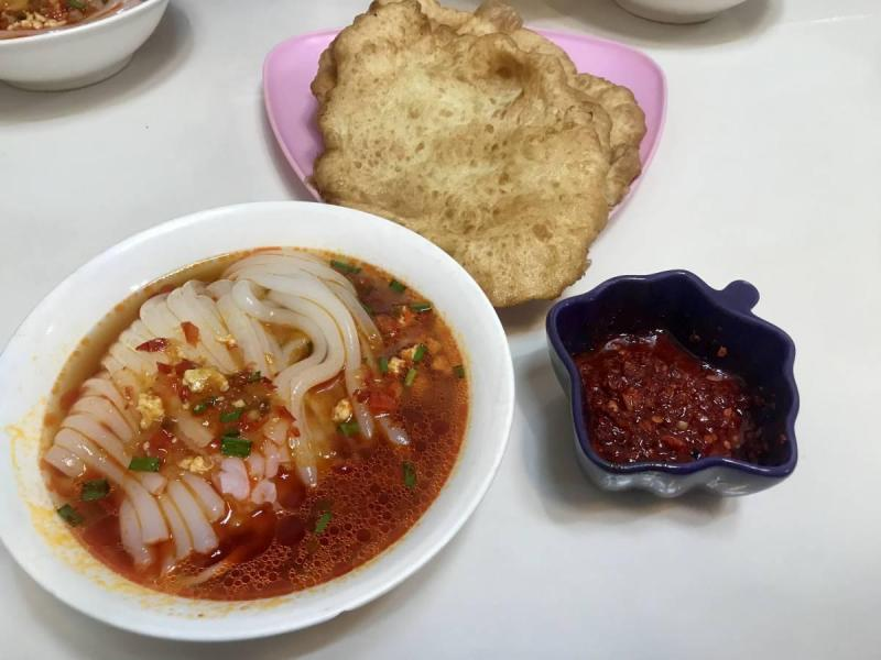 Bowl of ashlan-fu with bread and hot sauce on the side