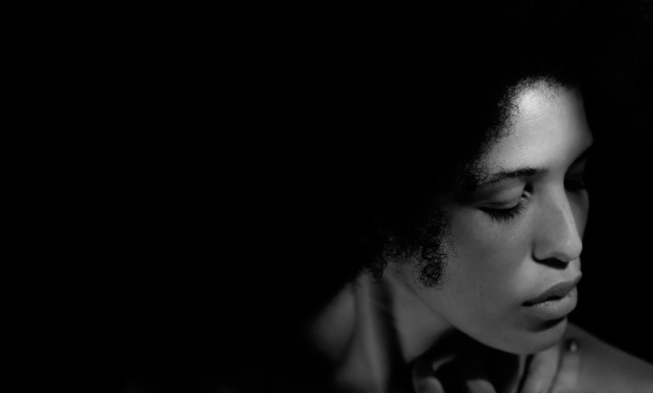 Black and white image of a light-skinned black woman's head and shoulders are visible against a very dark background. She is looking down and to the right of the image, and looks pensive or upset.