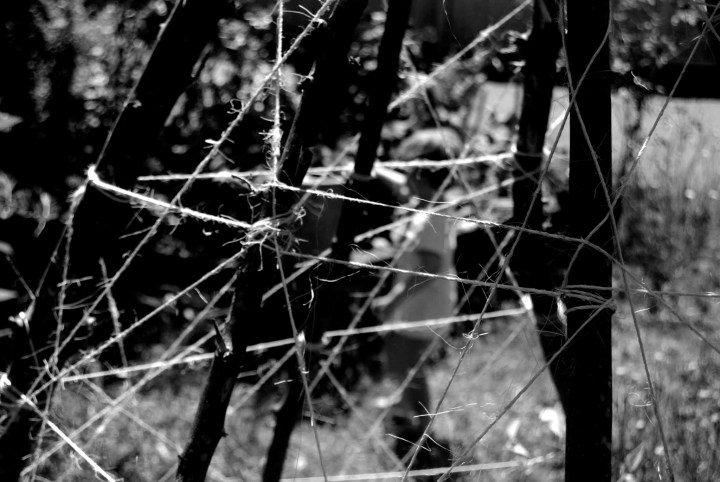 a small child stands blurred behind a crisply focused tangle of sticks and strings. Black and white, oudoors in the sunshine