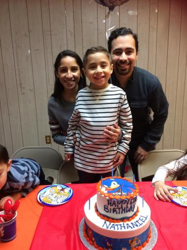 The happy birthday boy with mommy and daddy