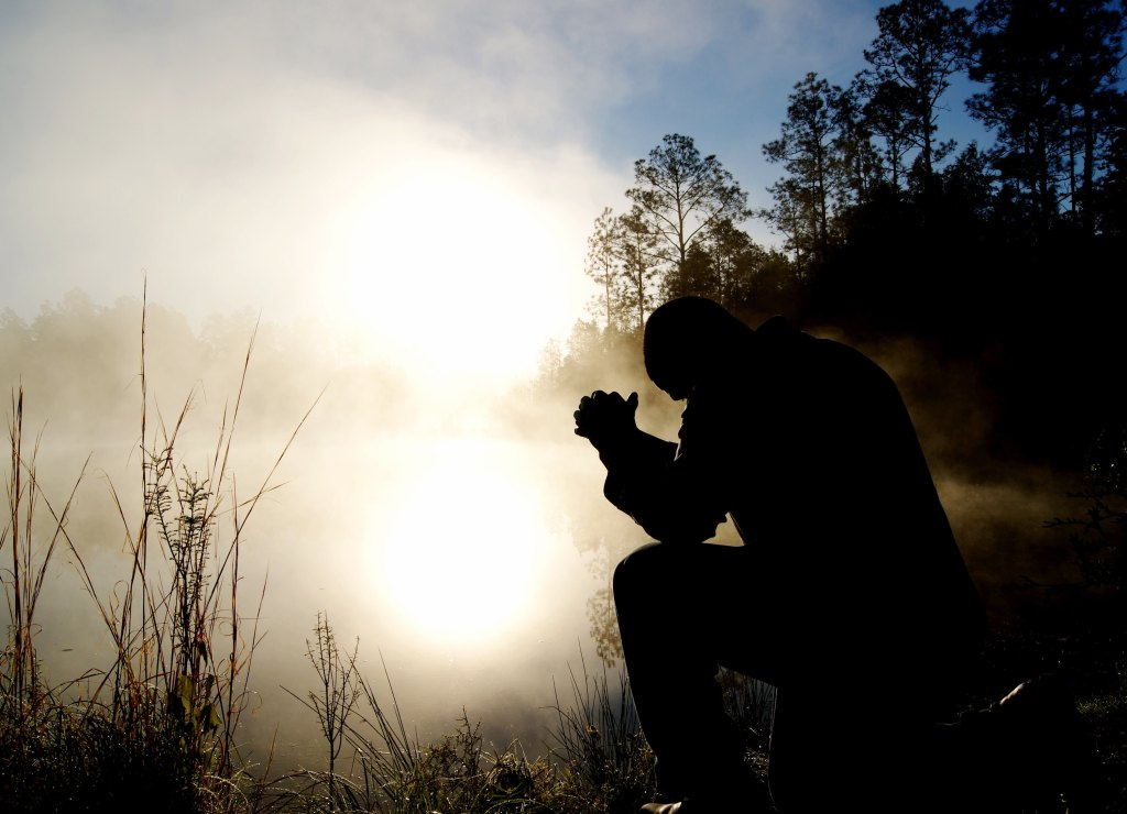 An individual kneeling on one knee and praying.