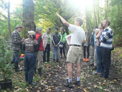 volunteers get instructions on where they should plant 8 species of trees; 80 total