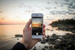 Een in de hand gehouden iPhone die en kustlandschap in beeld neemt