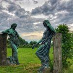 Twee groengrijze bronzen vrouwenbeelden die mekaar aanstaren. Ze staan in een grasveld en steunen beide met een elleboog op een massief houten sokkel. Achter één van de beelden is een stuik te zien en aan het einde van het grasveld staan bomen. Opvallend is de bijzonder dreigende wolkenlucht, waaruit elk moment een onweer kan losbarsten.