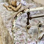Wassenbeeld van een stokoud uitgemergeld vrouwtje in een outfit die doet denken aan een trouwkleed. Ze ligt op een oud bed met metalen spijlen aan het hoofd- en voeteinde, op een laken met bloemetjesmotief. De spijlen afgebladderde van het voeteinde zijn prominent in de voorgrond aanwezig en zorgen voor een retro-sfeertje.