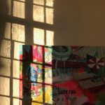 Schreeuwerig kleurrijk schilderij met drukke figuren tegen een gelige wand. Het invallend licht werpt een sterke schaduw van een venster, bestaande uit meerdere rechthoekige raamdelen, tegen de wand. Daardoor worden een aantal rechthoekige stukjes uit het schilderij fel belicht, terwijl de rest van het schilderij in een diepe schaduw baadt.