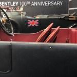 Een Bentley 3L TT Factory Repica met een prachtig roodleren interieur, met daarachter een Bentley 4.5 Litres waarop een Britse vlag prijkt. De auto's staan in een zwart decor met daarop het opschrift 'Bentley 100th Anniversary'