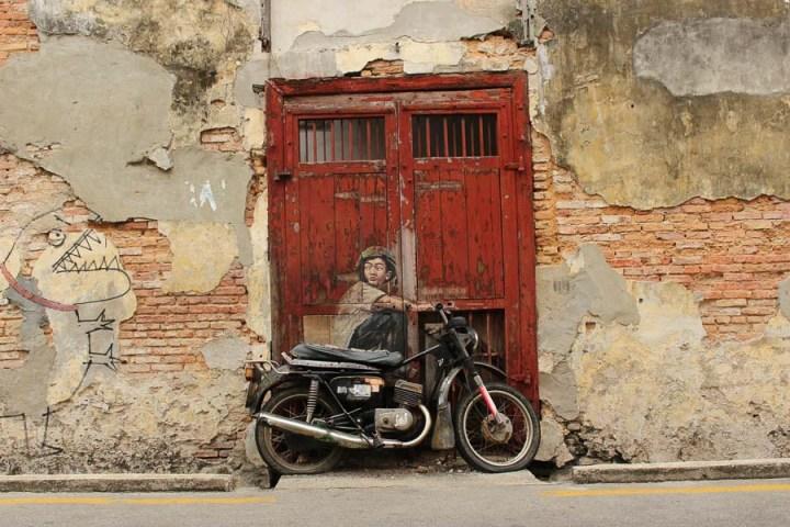 Mural en Georgetown. Niño pintado en una puerta roja.