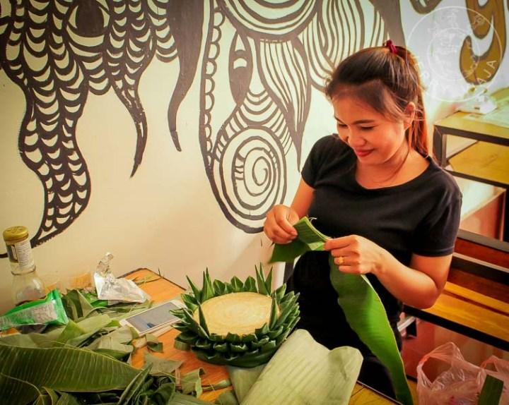 Mujer de Pakse realizando un hua fai (bote de tronco y hojas de banano) a mano.