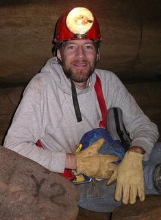 """Picture of Dennis Jerz, wearing a mining helmet, posing next to a rock labeled """"Y2."""""""
