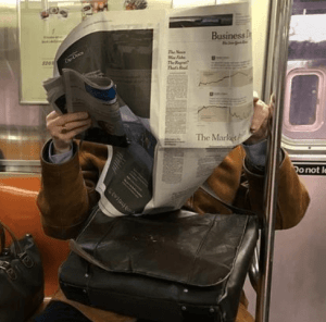 Image: A man reads a newspaper on a subway car.