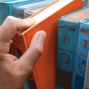 Closeup of a person's hand pulling a book off of a shelf.