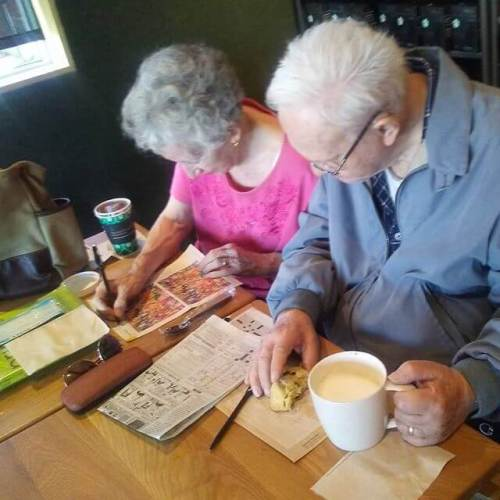 My parents doing their daily brain treasers in a coffee shop.