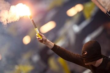 Passionate AIK supporter burning pyrotechnics.