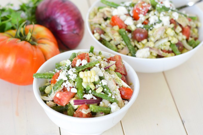 Fresh corn, tomatoes and green beans are tossed together with a whole shredded rotisserie chicken to make a delicious summer vegetable salad. A cilantro and jalapeno dressing adds tons of flavor!