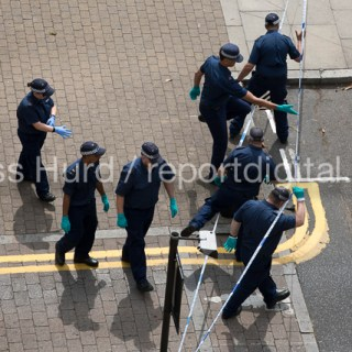 Police forensic team searching the area after a stabbing of a young man in Knapp Road, E3, East London.