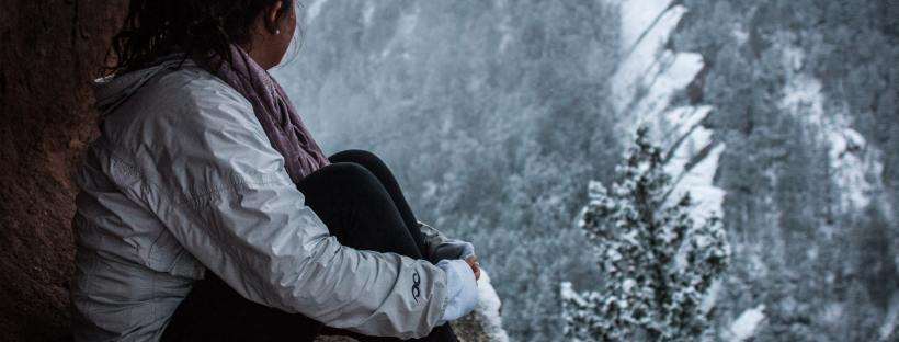 woman sitting on mountain looking at snow