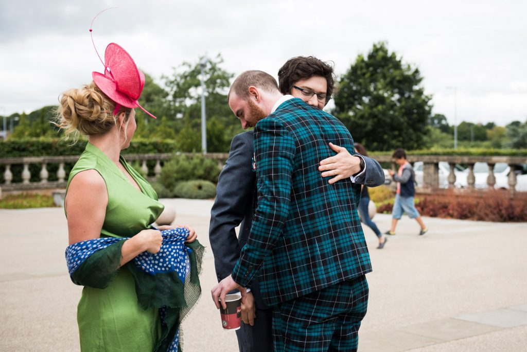Quirky Groom wearing tartan suit hugs wedding guest Berkshire theatre wedding