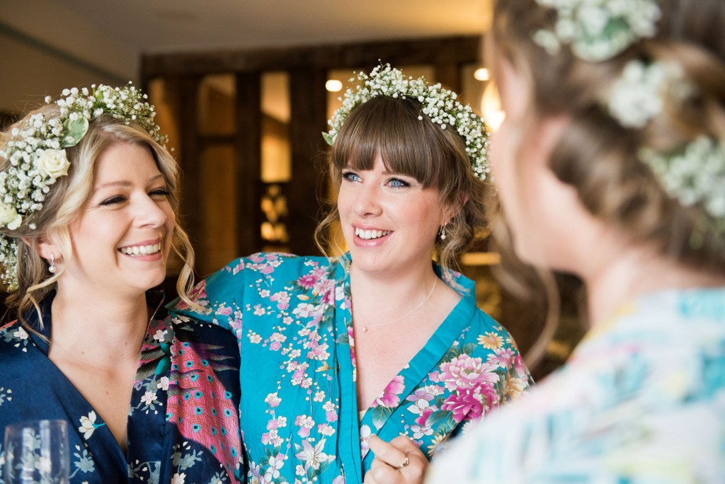 Smiling bride with bridesmaids wearing floral robes and boho Gypsophila crowns