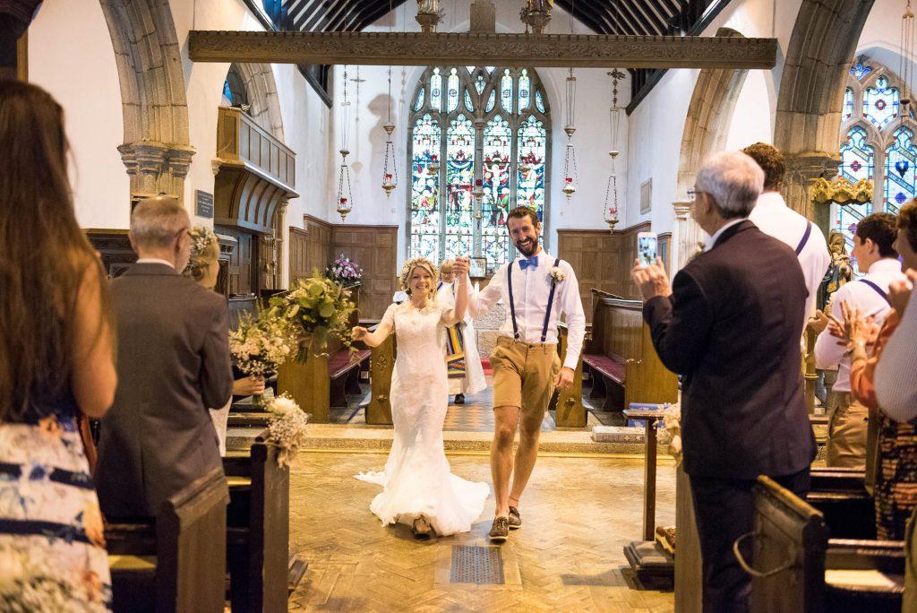 Boho bride with groom walk church aisle Cornwall
