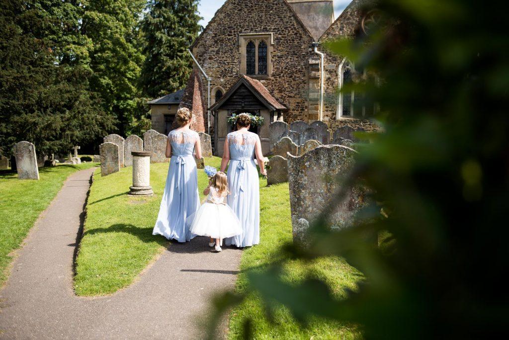 Coast bridesmaids walk with flower girl