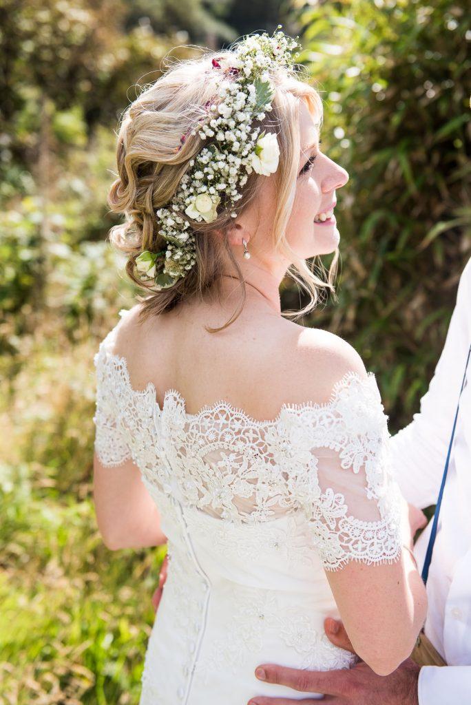 Smiling boho bride wearing Gysophila floral crown Cornwall wedding