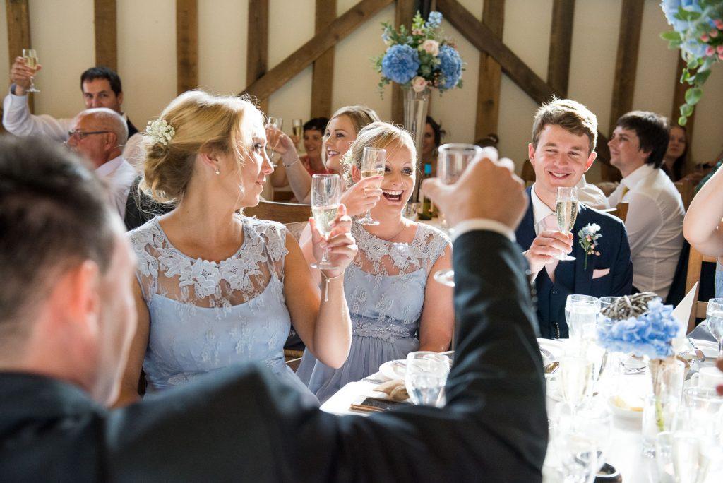 Coast bridesmaids raise champagne glass for toast