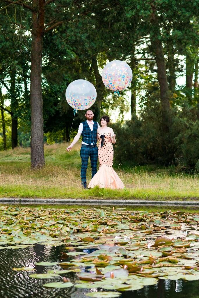 Creative wedding portrait alternative dressed bride with groom holding colourful balloons Berkshire