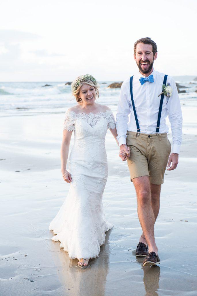 Happy boho bride with groom walking on Cornwall beach