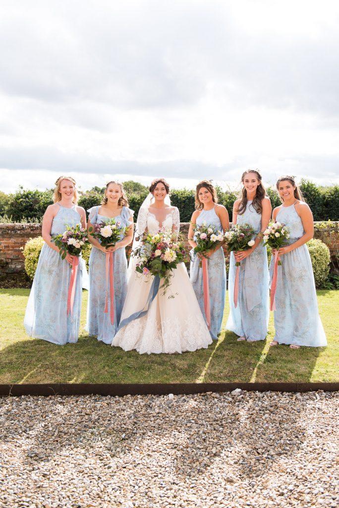Bride with pastel blue bridesmaids Norfolk Barn Wedding