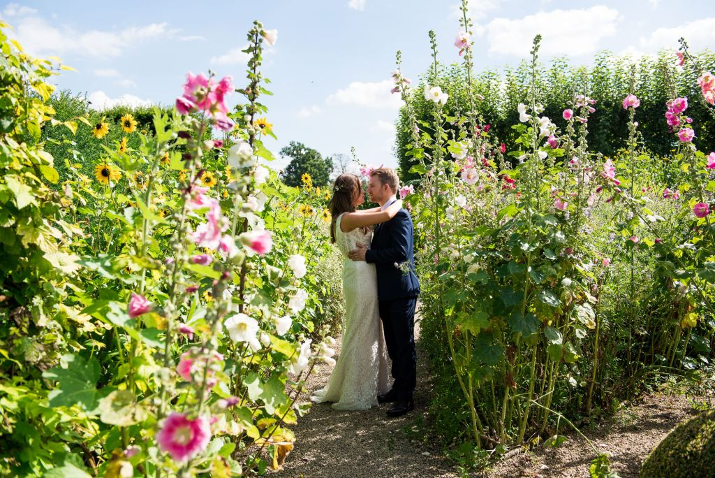 Bride and groom amongst the wild garden at Loseley Park
